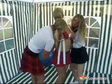 Three teenage girls in schoolgirl uniforms are playing with each other in a party tent. They start undressing each other, letting their hands roam everywhere. Once naked they please each other with various toys.video